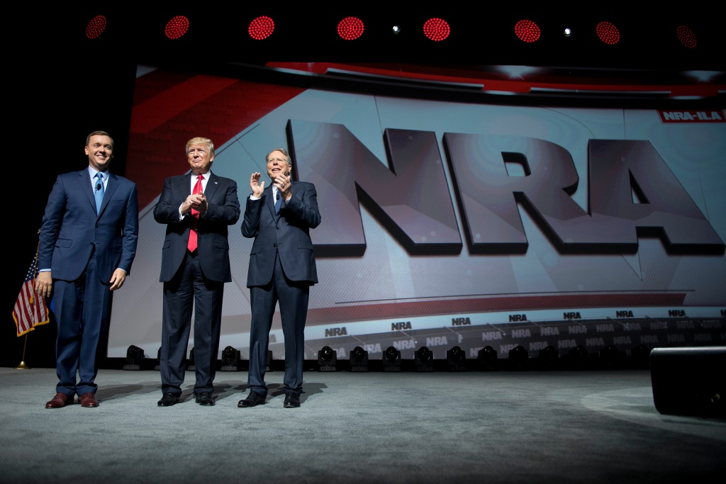 US President Donald Trump stands with National Rifle Association (NRA) President Wayne LaPierre (right) and NRA-ILA Executive Director Chris Cox (left) during the NRA Leadership Forum in Atlanta, Georgia on April 28, 2017.