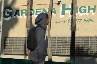 A student walks past the entrance to Gardena High School in Gardena, California January 18, 2011 after two students were shot when a gun went off accidentally in a classroom.