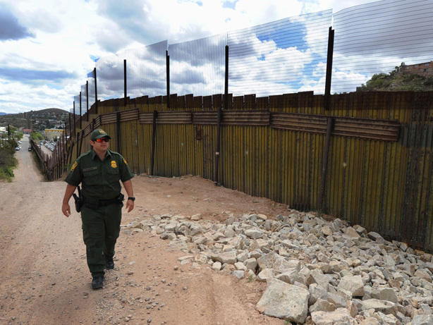 A U.S. Border Patrol officer keeps watch over the fence that divides the U.S. from Mexico in the town of Nogales, Ariz.