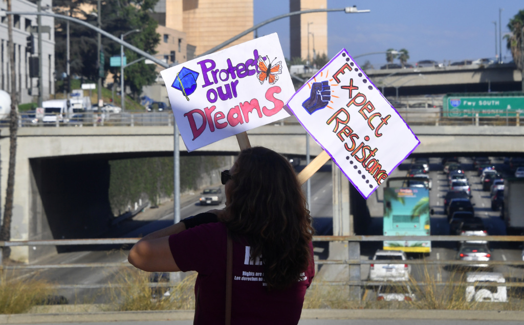 Volunteers from The Coalition for Humane Immigrant Rights (CHIRLA) protest with banners and placards over a freeway in Los Angeles, California on August 28, 2017.