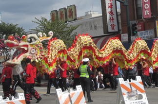 Volunteers at the parade walk the dragon down to the beginning of the parade route.