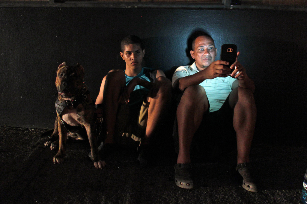 A man checks his cell phone next to a road at night in one of a few places with cell signal in San Juan, Puerto Rico after Hurricane Maria.