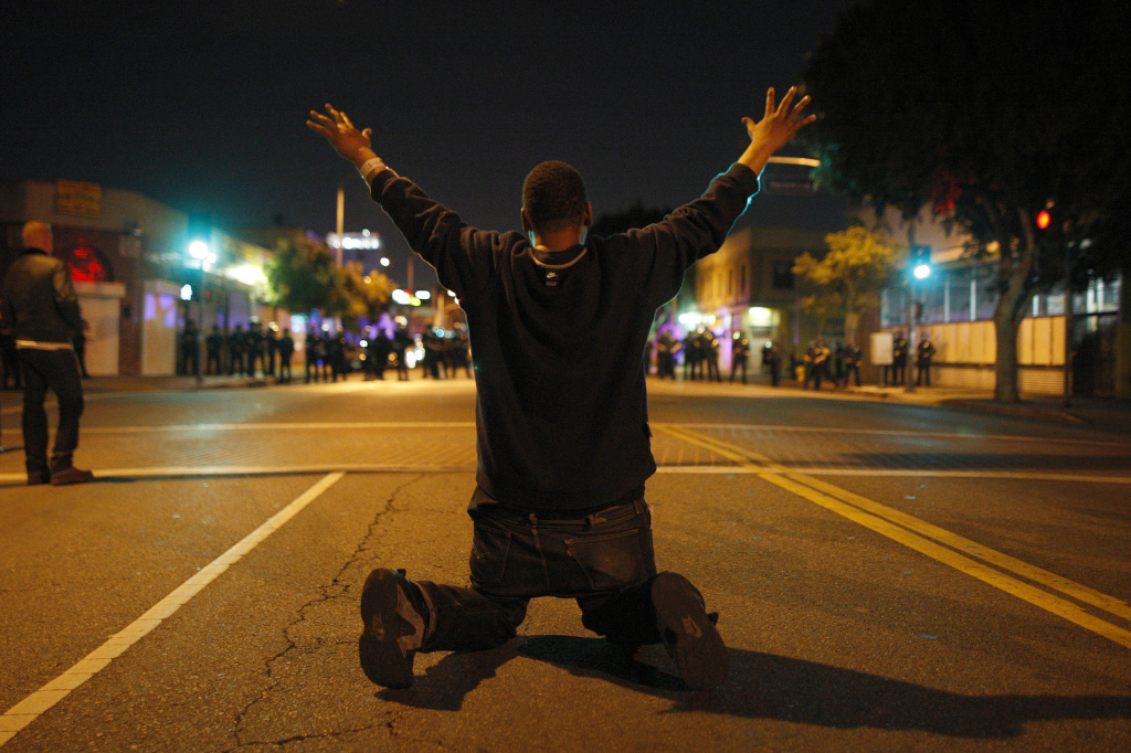 In this file photo, a man kneels in the street before a line of police officers about to charge at protesters reacting to the grand jury decision not to indict a white police officer who had shot dead an unarmed black teenager in Ferguson, Missouri, in the early morning hours of November 25, 2014 in Los Angeles, California. Legislation advanced in the California Assembly on Thursday, July 16, 2015, is among several bills introduced in response to nationwide protests over police slayings of unarmed black men.