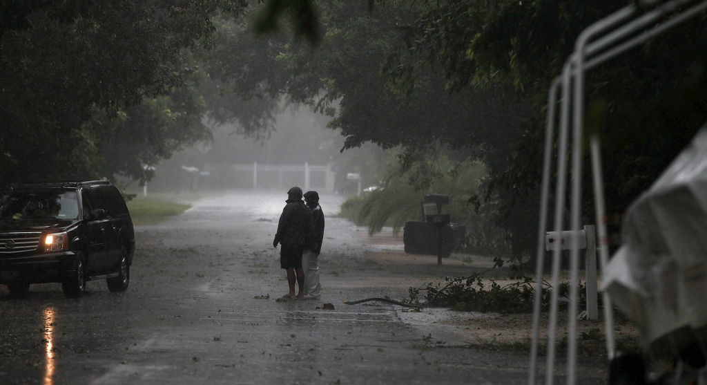 People stand near downed branches as Tropical Storm Isaac begins to move ashore on August 26, 2012 in Marathon, Florida.