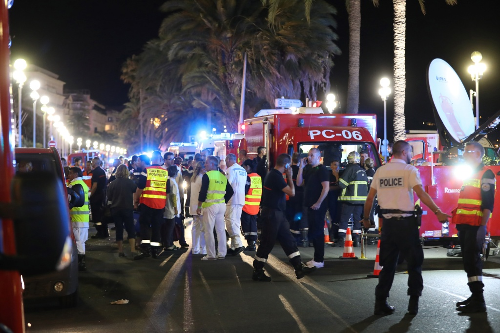 Police officers, firefighters and rescue workers are seen at the site of an attack on July 14, 2016, after a truck drove into a crowd watching a fireworks display in the French Riviera town of Nice.