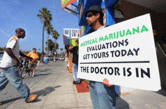A man holds a placard advertising medical marijuana outside an evaluation clinic on Venice Beach in Los Angeles on October 9, 2009.