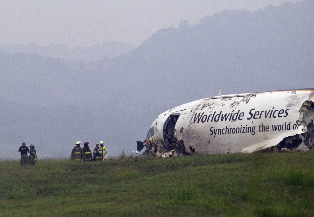 Fire crews work the scene of a UPS cargo plane crash at the Birmingham-Shuttlesworth International airport, Wednesday, Aug. 14, 2013, in Birmingham, Ala.