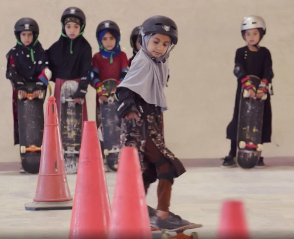 Students wearing headscarves and helmets learn to navigate traffic cones in a scene from the Oscar-winning documentary,
