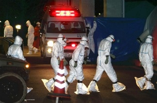 Workers in radiation protection suits prepare for the decontamination of two nuclear plant workers who were exposed to high levels of radiation, upon their arrival at the Fukushima Medical University hospital at Fukushima city on March 24, 2011.