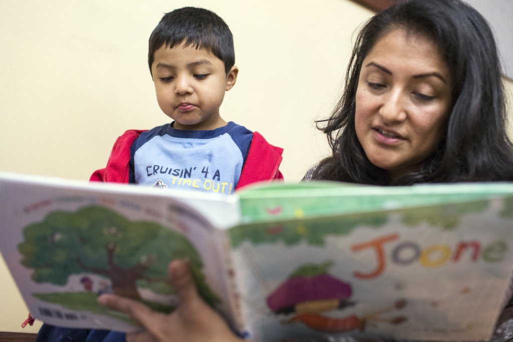 Marisa Gonzalez and her son, 3-year-old Bradley Gonzalez, read a book during a parent training put on by the Children's Bureau at the Pico Union Branch Library.