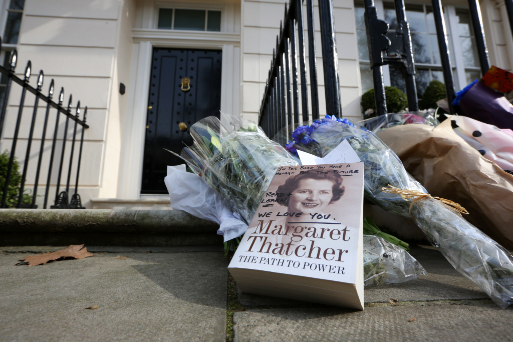A book about former Prime Minister Margaret Thatcher with a message on the cover is left next to floral tributes outside the residence of Baroness Thatcher in Chester Square on April 8, 2013 in London, England. Lord Bell, spokesperson for Baroness Margaret Thatcher, announced in a statement that the former British Prime Minister died peacefully following a stroke on 8th April, aged 87.