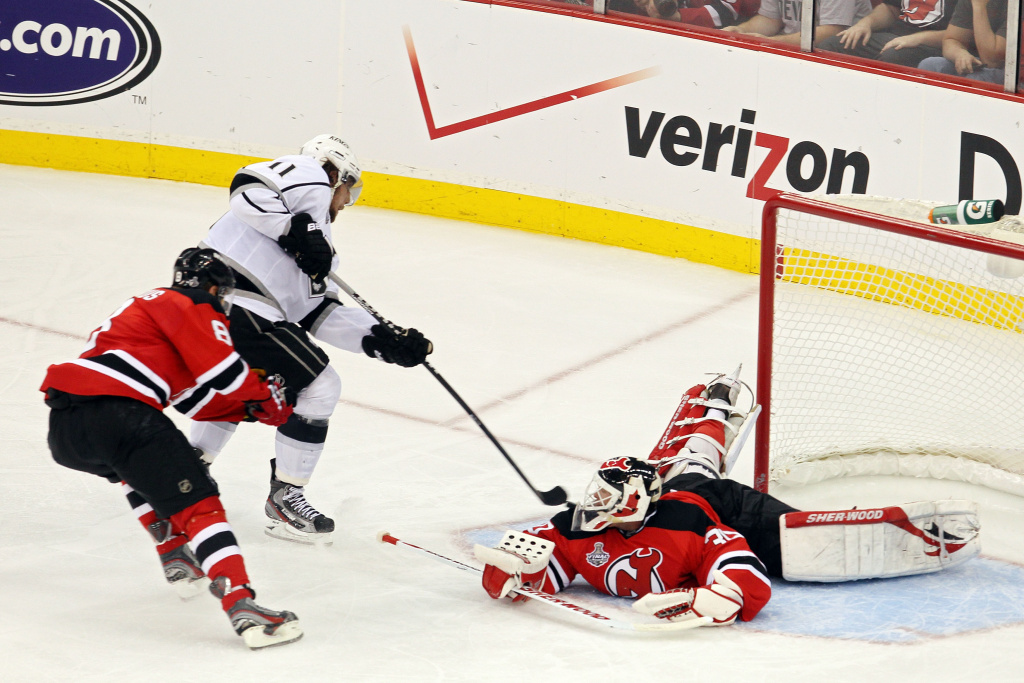 Anze Kopitar #11 of the Los Angeles Kings shoots the game winning goal in overtime against Dainius Zubrus #8 and Martin Brodeur #30 of the New Jersey Devils during Game One of the 2012 NHL Stanley Cup Final.