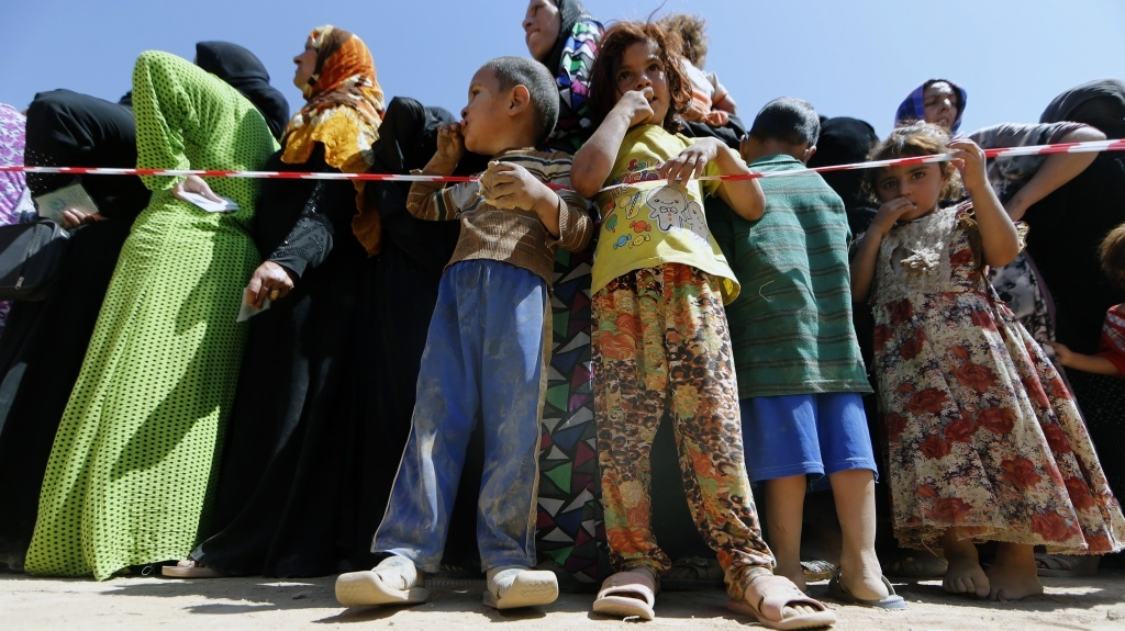 Displaced Iraqi children line up with their mothers Tuesday to register at a temporary camp for people fleeing violence in northern Iraq.