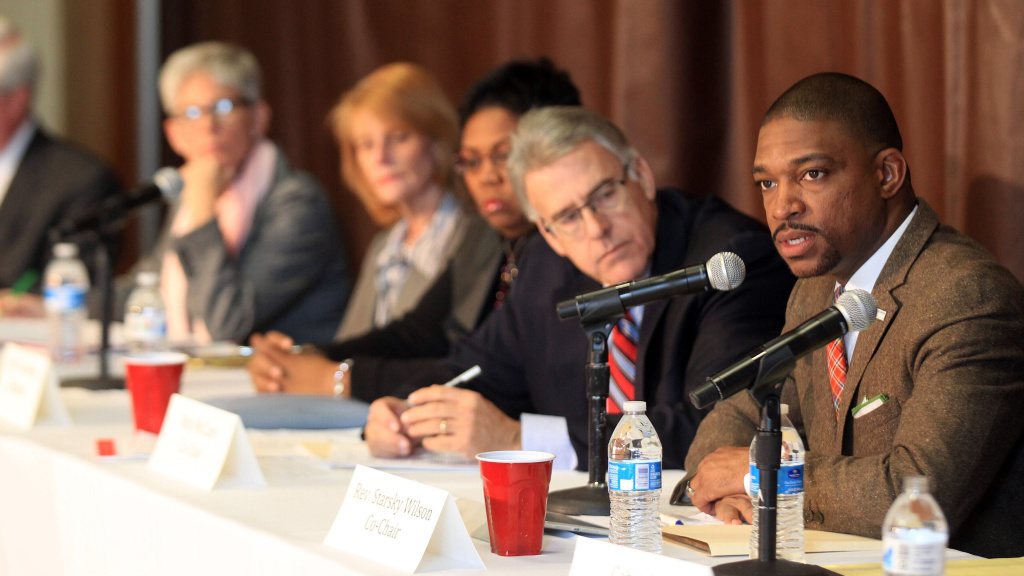 Ferguson Commission Co-Chair Rev. Starsky Wilson makes his opening remarks as Co-Chair Rich McClure and other commissioners listen during the commission's first meeting in Ferguson, Mo., Monday.