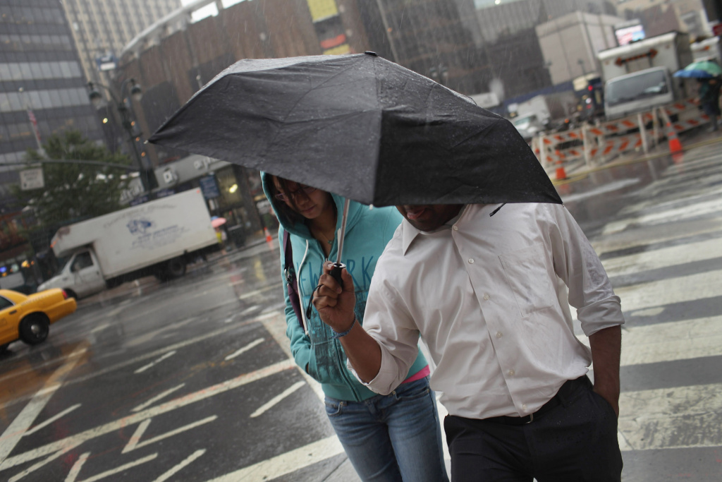People walk under an umbrella during a mid-season storm. Rain run-off washes a swirl of chemicals, trash, gum and debris into the drainage system, which in turn makes its way to major bodies of water.