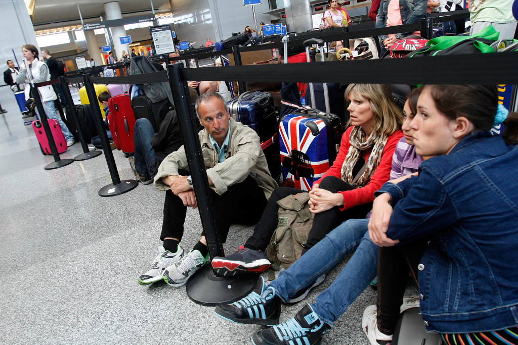 (L-R) Alphonse Roig, his wife Christine Roig, and daughters Nanine Roig and Lana Roig wait at the British Airways counter for it to reopen at San Francisco International Airport July 6, 2013 in San Francisco, California.