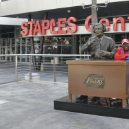 Darrell Bailey, known as Clipper Darrell, sits with the Chick Hearn statue in the Staples Center courtyard