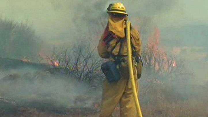 A firefighter fights the Riverside-county blaze, now contained at 75 percent.