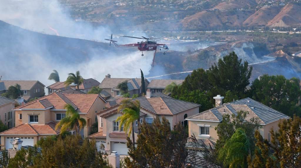 A helicopter drops water near homes at the Anaheim Hills neighborhood in Anaheim on Oct. 9, 2017.