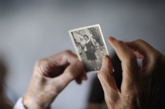 A woman, suffering from Alzheimer's desease, looks at an old picture of herself.