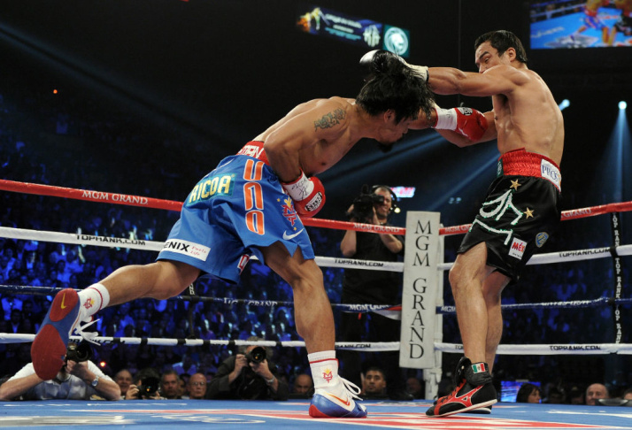Manny Pacquiao knocks back Juan Manuel Marquez with a left to the body in the first round during the WBO world welterweight title fight at the MGM Grand Garden Arena on November 12, 2011 in Las Vegas, Nevada.