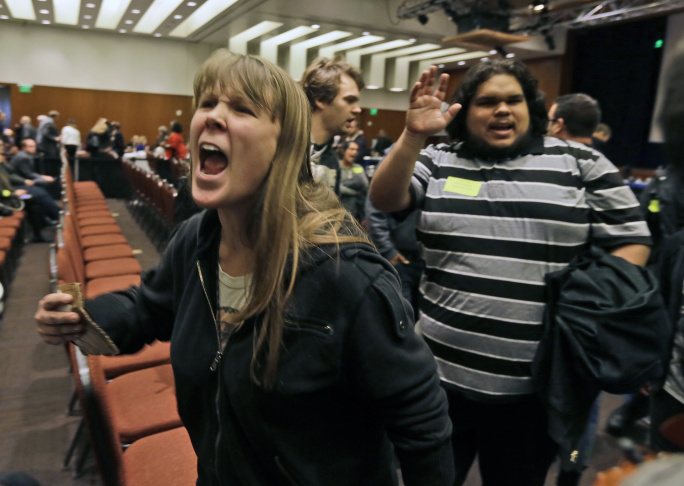 Amelia Itayre, 23, and Sebastian Cano, 21, students at University of California Davis, react after the vote to raise tuition fees was announced during the UC Regents meeting in San Francisco, Thursday, Nov. 20, 2014. The Regents approved raising tuition by as much as 5 percent in each of the next five years unless the state devotes more money to the 10-campus system.