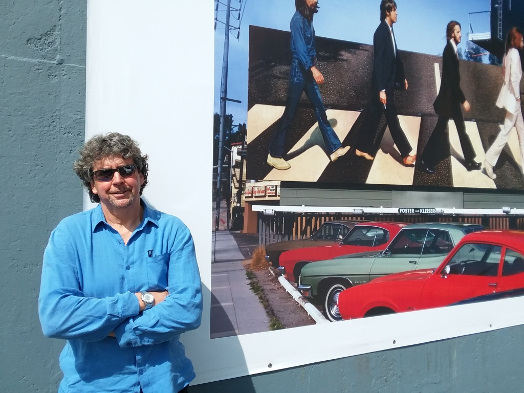Robert Landau poses in front of his photo of the Beatles.