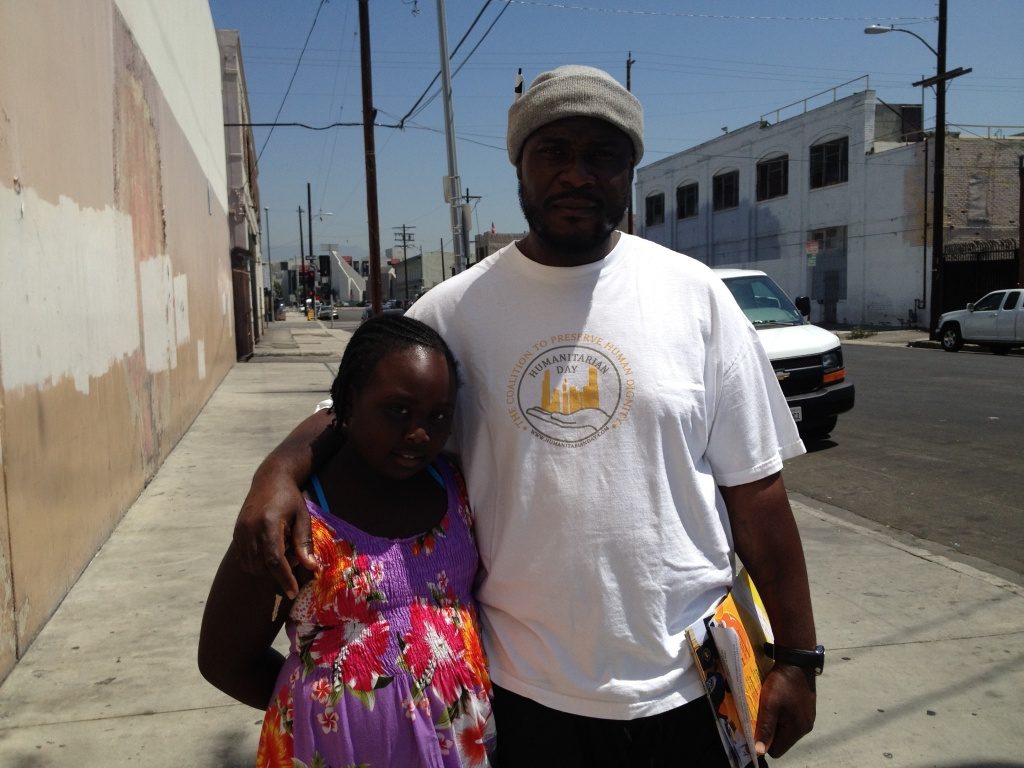 Umar Hakim and 8 year-old daughter, Aneesah, distributing flyers for Humanitarian Day on August 12th, in downtown Los Angeles.