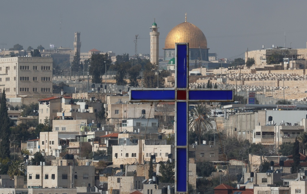 A view the Dome of the Rock and a cross is seen from behind the wall separating East Jerusalem from the palestinian village of Abu Dis.