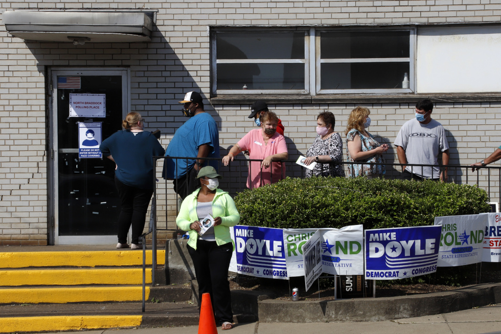 Voters stand in line as they wait to cast their ballots during primary voting in Braddock, Pa., on Tuesday. Problems with absentee ballots and a smaller number of polling places led to long lines in several states as primary elections that were delayed by the coronavirus resumed.
