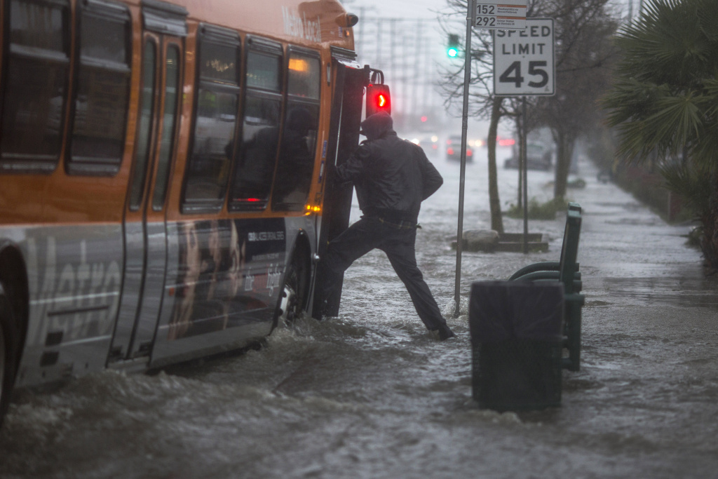 A man boards a bus on a flooded street as a powerful storm moves across Southern California on February 17, 2017 near Sun Valley, California.