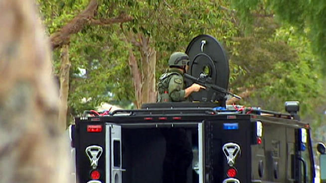 July 5, 2012: An armed SWAT officer is seen here, stationed outside a Long Beach home.