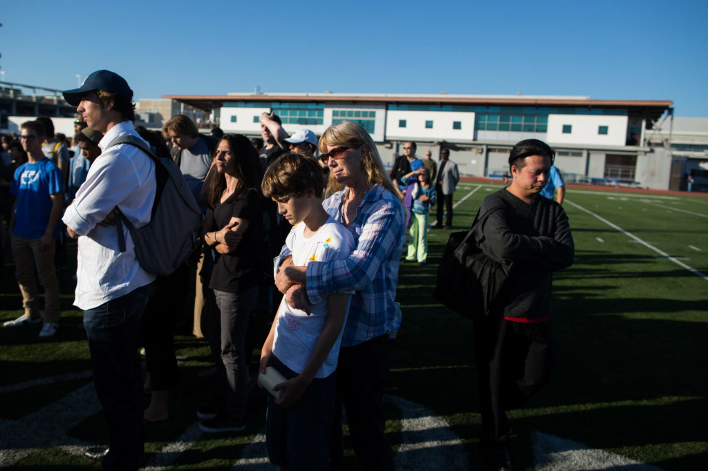 Mourners watch a vigil for five people killed in a mass shooting that ended at Santa Monica College.