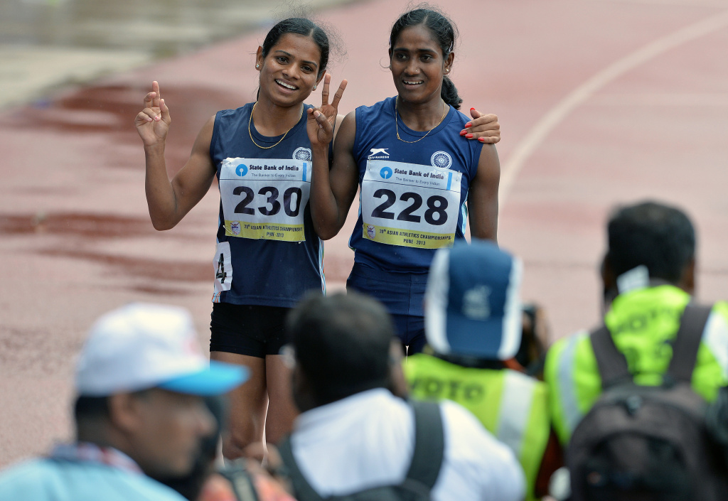 Women's 200 meters respective silver and bronze medal winners from India Asha Roy (R) and Dutee Chand flash victory signs after their race on the fifth and the final day of the Asian Athletics Championship 2013 at the Chatrapati Shivaji Stadium in Pune on July 7, 2013.