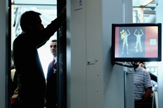 A man demonstrates a check by a full body scanner at Hamburg Airport in Hamburg, Germany.