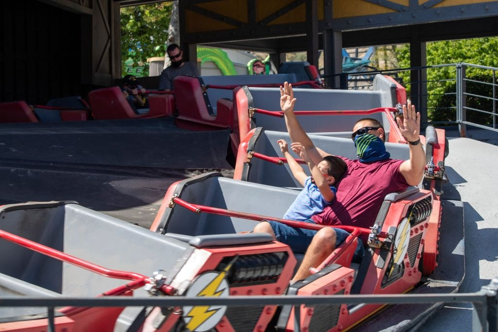 Visitors wearing face masks enjoy the Flash Speed Force ride at the theme park Six Flags Magic Mountain on the day of the park's re-opening, April 1, 2021, in Valencia, California.