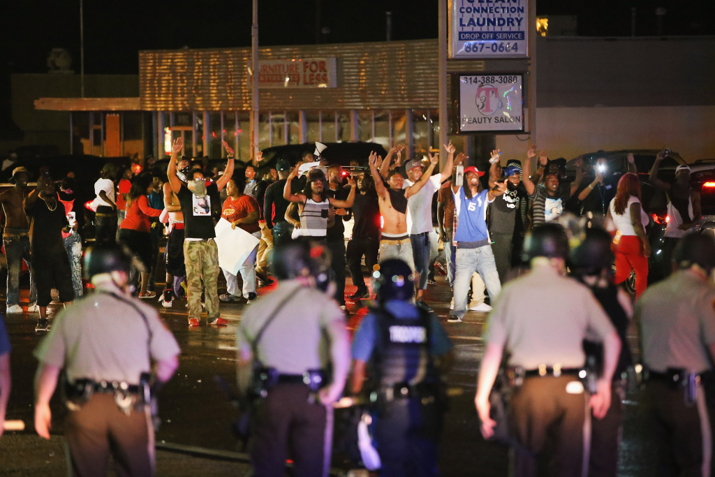 Demonstrators taunt police during a protest over the shooting death of Michael Williams on Aug. 15, 2014 in Ferguson, Missouri, Police shot pepper spray,  smoke, gas and flash grenades at protesters before retreating. Several businesses were looted as the county police sat nearby with armored personnel carriers (APC). Violent outbreaks have taken place in Ferguson since the shooting death of Brown by a Ferguson police officer on Aug. 9.