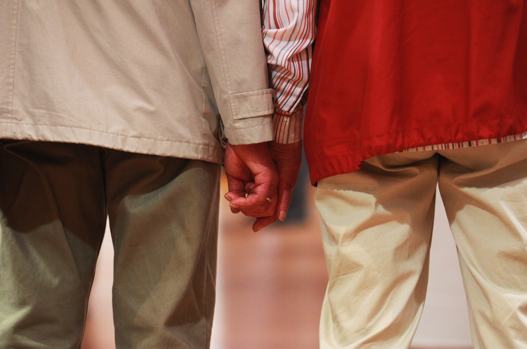 """An elderly couple hold hands at a trade fair at the """"Seniorentag 2012"""" senior citizens convention on May 3, 2012 in Hamburg, Germany."""