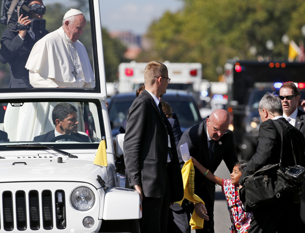 Sophie Cruz, 5, of suburban Los Angeles reaches to give Pope Francis a letter and T-shirt during a parade in Washington on Wednesday. The massive security apparatus protecting Pope Francis on his historic, six-day trip to the U.S. got its first test Wednesday as the girl with a gift for the pontiff made her way through a security barrier and onto his parade route.