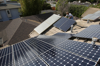 Employees of Solar Forward install solar electric panels on a residential rooftop on February 27, 2009 in Santa Monica, California.