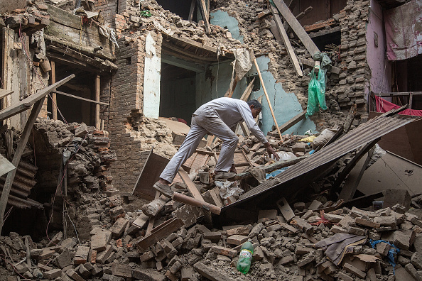 BHAKTAPUR, NEPAL - APRIL 26:  A man climbs on top of debris after buildings collapsed on April 26, 2015 in Bhaktapur, Nepal. A major 7.8 earthquake hit Kathmandu mid-day on Saturday, and was followed by multiple aftershocks that triggered avalanches on Mt. Everest that buried mountain climbers in their base camps. Many houses, buildings and temples in the capital were destroyed during the earthquake, leaving thousands dead or trapped under the debris as emergency rescue workers attempt to clear debris and find survivors.  (Photo by Omar Havana/Getty Images)
