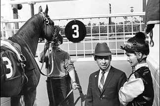 At Hollywood Park in 1966, trainer John Longden gives jockey Bill Shoemaker riding instructions for