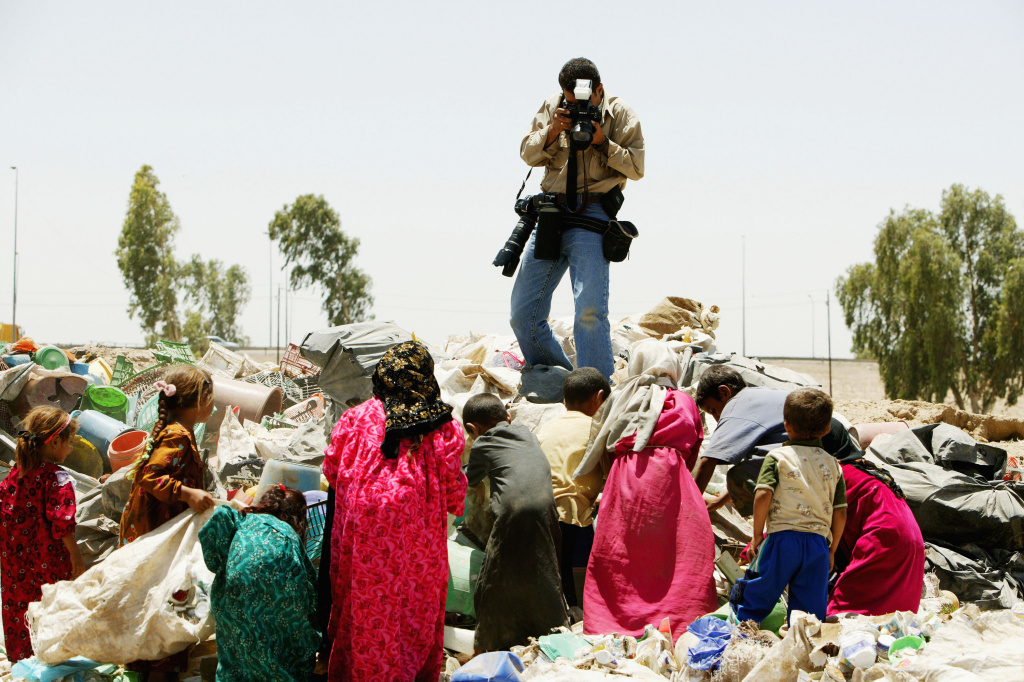 Freelance Iraqi photographer Wathiq Khuzaie, 32,  working for Getty Images, shoots a photograph of poor Iraqis who live among the garbage dumps June 30, 2004 outside of Baghad, Iraq. Khuzaie has received eight national and international awards for his photojournalism work over the years.