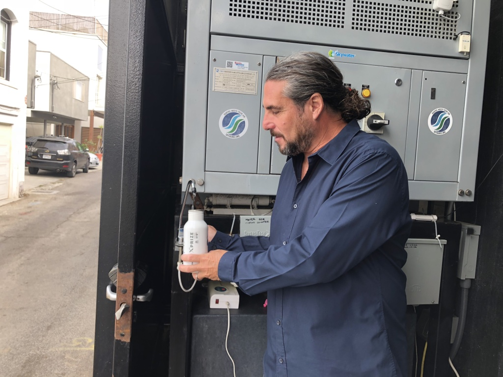 Architect David Hertz fills his bottle with water created by his atmospheric water generator.
