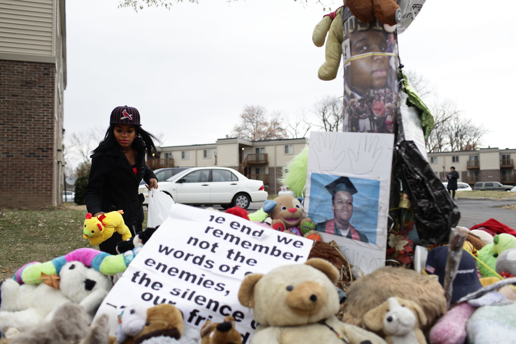Marneisha Jones places a stuff animal at a makeshift memorial for Michael Brown, an 18-year-old black male teenager fatally wounded by Darren Wilson, a white Ferguson Police officer on August 9, 2014.