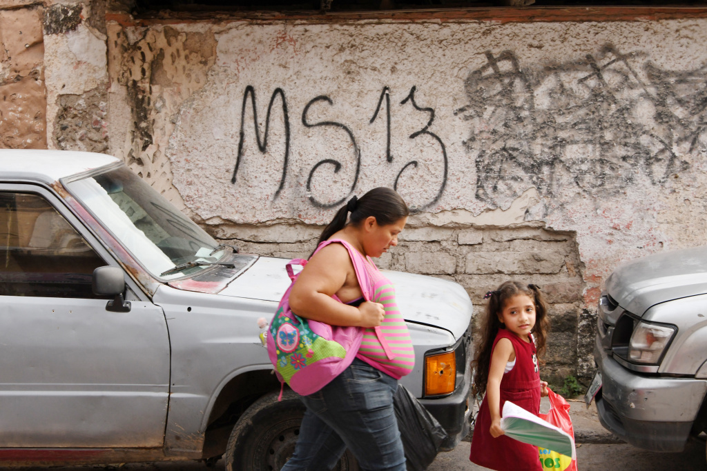 FILE: Residents pass by a grafitti made by the Mara Salvatrucha gang in the MS-13-controlled El Bosque neighborhood in Tegucigalpa, Honduras, on May 9, 2017. Many Hondurans in the U.S. who live and work here legally under temporary status worry they will need to return to their homeland.