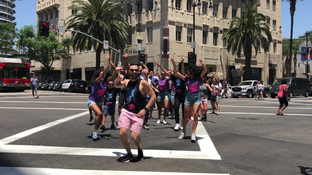 LA officials and the cast of On Your Feet christens the new diagonal crosswalk with a Conga line.
