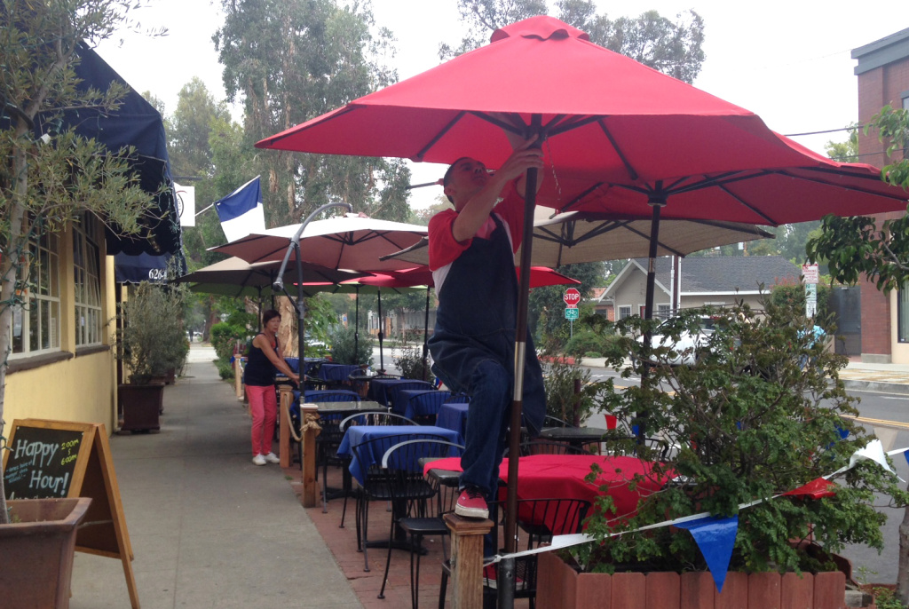 Nicole Grandjean (background left) and a colleague set up for their Bastille Day celebration outside Nicole's Gourmet Market and Cafe in South Pasadena on July 15, 2016.