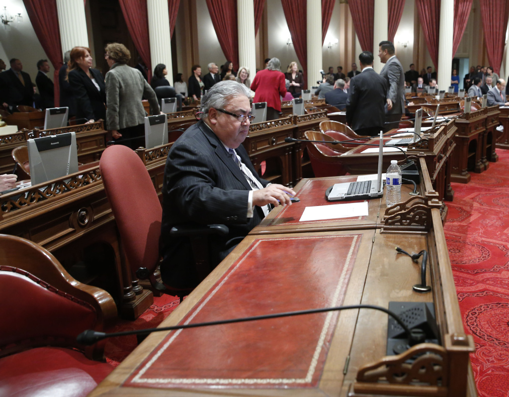 State Sen. Ron Calderon, D-Montebello, sits at his desk during the first Senate session of the new year at the Capitol in Sacramento, Calif., Monday, Jan. 6 2014.  Calderon, whose Sacramento offices were raided by the FBI in June, had his assigned seat in the Senate chambers moved from front-and center to a far corner, next to a vacant desk.  He also has been stripped of all committee assignments in the wake of an investigation for allegedly accepting nearly $90,000 from an undercover FBI agent.