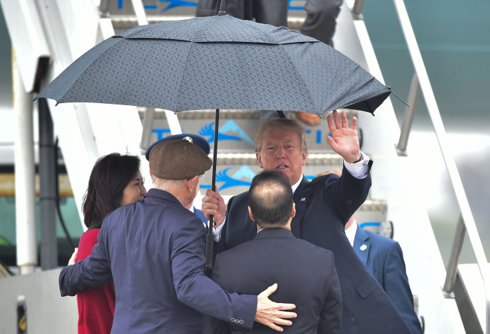 President Donald Trump waves as shelters from the rain under an umbrella as he arrives in Los Angeles on March 13, 2018.